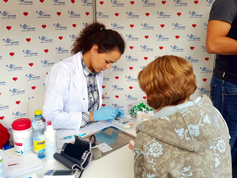 Personel medyczny sprawdza wyniki na CardioChek PA. 4 parametry kardiologiczne z małej próbki z palca.