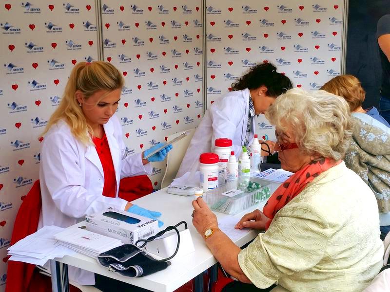 Personel firmy Grupa Medyczna Puls na stoisku firmy Servier, używa CardioChek PA z Panelem Kardiologicznym
